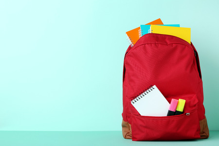Red backpack with school supplies on mint background Stockfoto