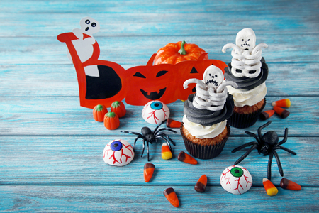 Halloween cupcakes with skeletons and candies on blue wooden table