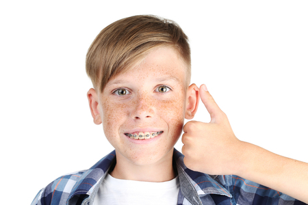 Young boy with dental braces on white background