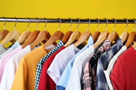 Cintres en bois avec des vêtements sur fond jaune Banque d'images