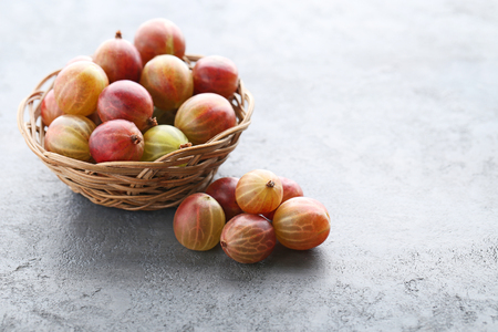 Ripe gooseberries fruit in basket on grey wooden table