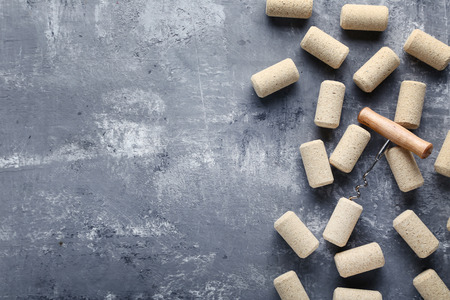 Wine corks with corkscrew on grey wooden table Stock Photo
