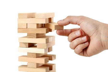 Mâle main jouant jeu de tour de blocs de bois sur fond blanc