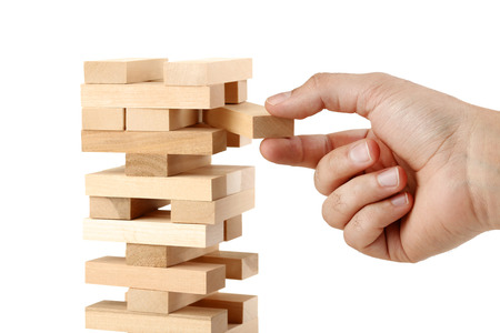 Male hand playing wooden blocks tower game on white background Foto de archivo