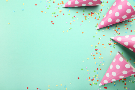 Birthday paper caps with confetti on mint background