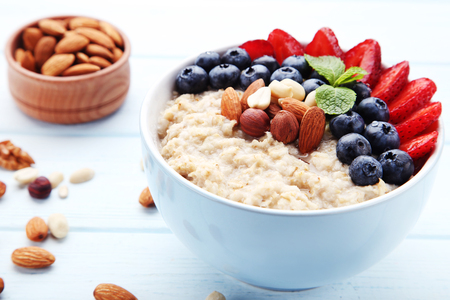 Oatmeal with berries and nuts in bowl on wooden table