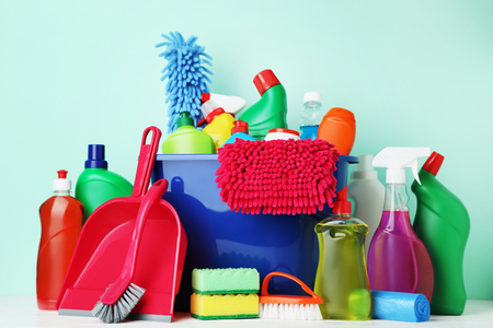 Bottles with detergent and cleaning tools on mint background