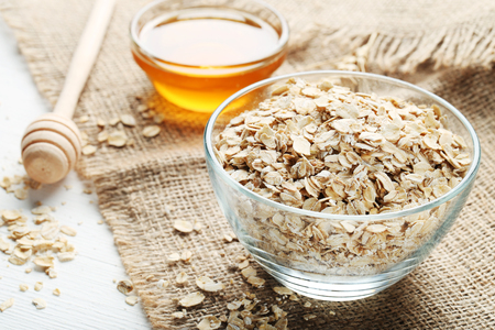 Oatmeal in bowl with honey on wooden table