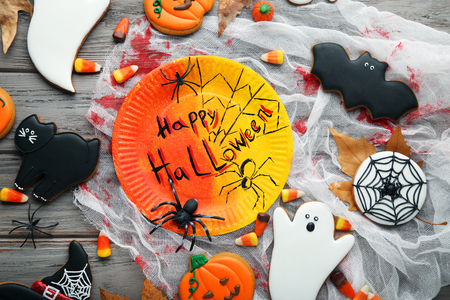 Halloween gingerbread cookies with candies and plate on wooden table