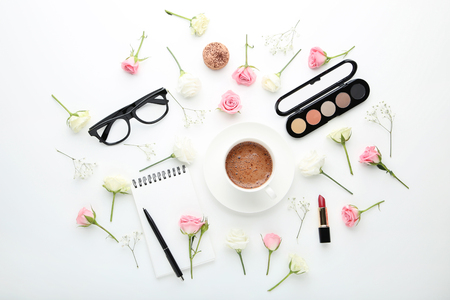Flowers with cup of coffee and makeup cosmetics on white background Stock Photo