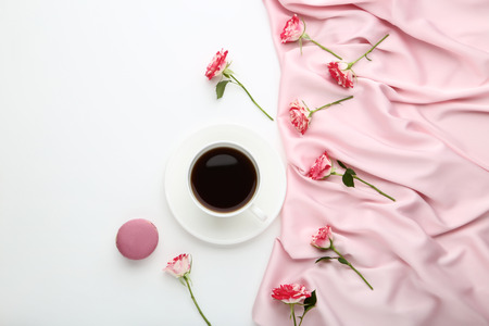 Rose flowers with cup of coffee and satin fabric on white background 免版税图像