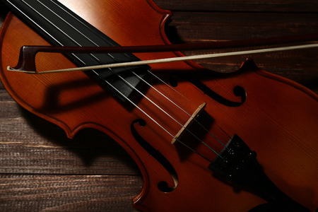 Violin with bow on brown wooden table