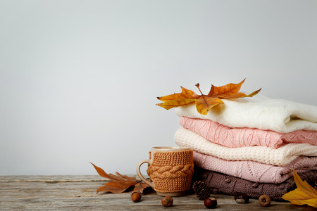 Stack of knitted sweaters with cup of tea and autumn leafs