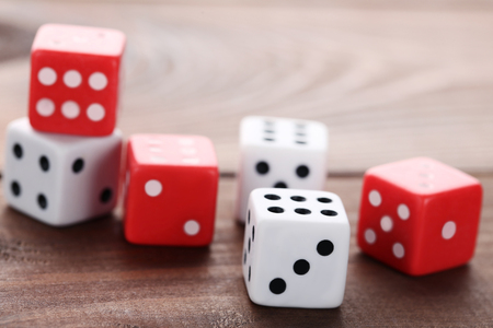Colourful dice on brown wooden table Stock Photo