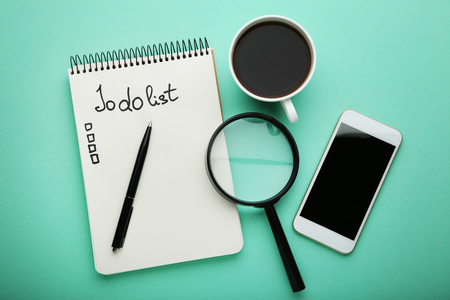 To do list in notepad with cup of coffee, smartphone and magnifying glass on mint background