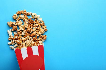 Caramel popcorn in striped bucket on blue background Stock Photo