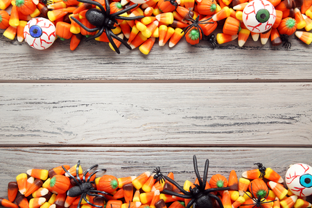 Halloween candy corns with black spiders on wooden table
