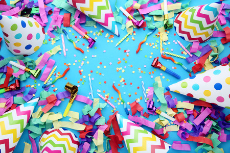 Birthday paper caps with confetti and blowers on blue background