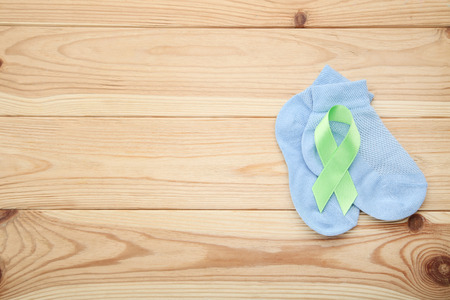 Green ribbon with blue baby socks on wooden table. Medical concept 스톡 콘텐츠