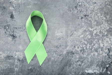 Green ribbon on grey background. Medical concept