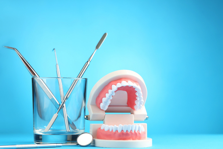 Teeth model with dental tools in glass on blue background