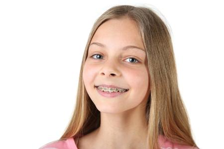 Niña sonriente con aparatos dentales sobre fondo blanco.