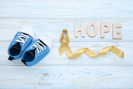 Golden ribbon with baby shoes. Children cancer concept