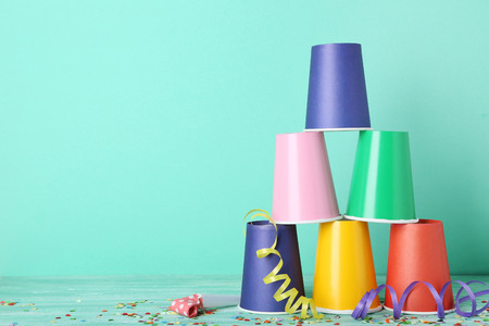 Colorful paper cups with confetti and blower on mint background