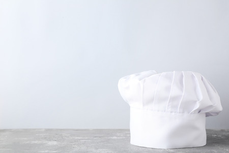 Chef hat on grey wooden table Stockfoto