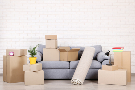 Cardboard boxes with household stuff and grey sofa on brick wall background