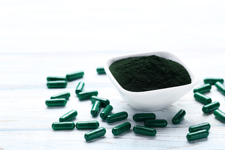 Spirulina powder and capsules on white wooden table Фото со стока