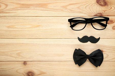 Black glasses with bow tie and paper mustache. Boss day concept
