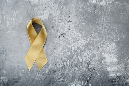 Golden ribbon on white background. Children cancer concept Stock Photo
