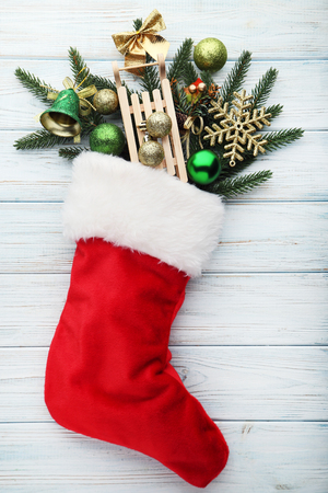 Red stocking with fir-tree branches and christmas decorations on wooden table Stock Photo
