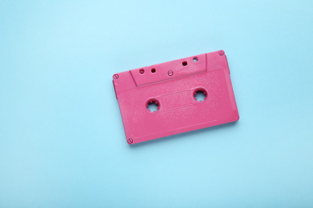 Pink cassette tape on blue background