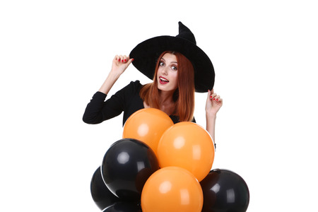Beautiful redhaired woman in halloween costume with balloons on white background