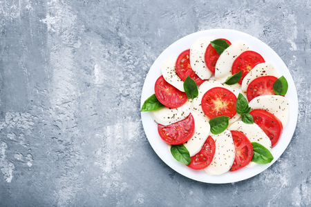 Mozzarella, tomatoes and basil leafs on grey wooden table