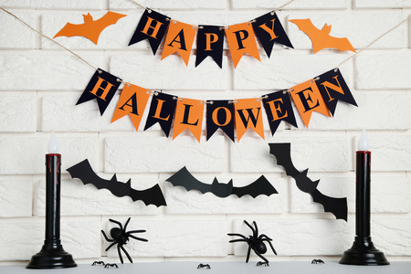 Paper halloween decorations with spiders and candles on brick wall background