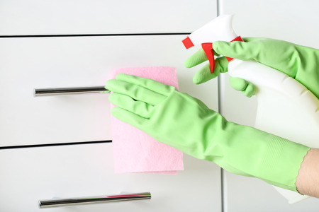 Hands in gloves with rag and bottle of detergent cleaning kitchen drawer Imagens
