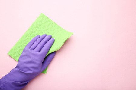 Hand in glove with sponge on pink background 免版税图像