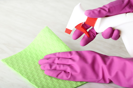 Hands in gloves with sponge and bottle of detergent cleaning kitchen table