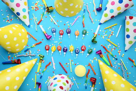 Birthday paper caps with candles and blowers on blue background