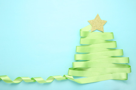 Green ribbon in shape of christmas tree on blue background