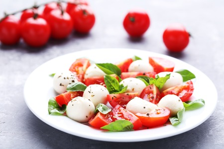 Mozzarella, tomatoes and basil leafs in plate on wooden table