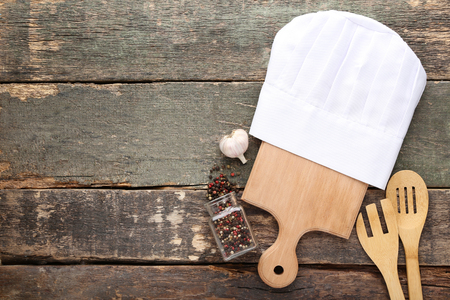 Chef hat with cutting board, pepper and garlic on grey wooden table