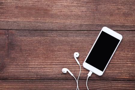 Smartphone with earphones on brown wooden table Stock fotó