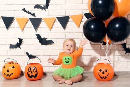 Baby girl in halloween costume with pumpkin buckets and balloons Stock Photo