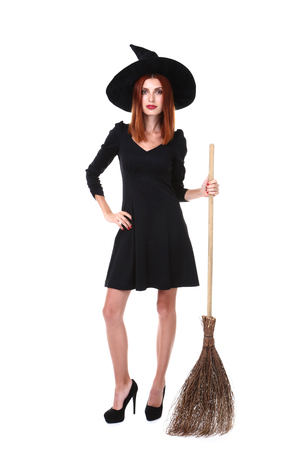 Beautiful redhaired woman in halloween costume with broom isolated on white background Stock Photo