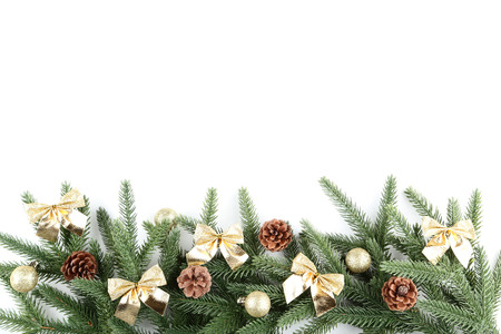 Christmas fir tree branches with baubles and cones on white background