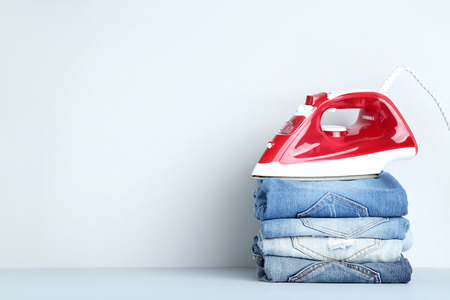 Stack of folded jeans with electric iron on grey background